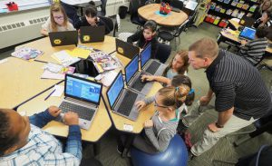 Technology consultant teacher Layne Henn works with fifth-grade students at Loess Hills Elementary School, a computer programming specialty school.