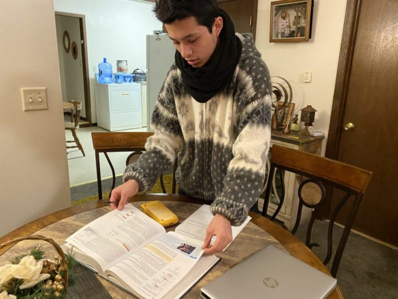 Cristian Rubio, 18, prepares to start his physics homework in the living room of his family's cozy home in Sioux City, Iowa. Photo by Lillian Mongeau, The Hechinger Report