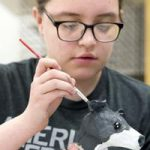 Bernadette Dumkrieger, a junior at North High School, works on a dog's head made of paper mache over a wire armature. Dumkrieger is one of numerous Sioux City art students exhibiting pieces as part of a group show at the University of South Dakota.