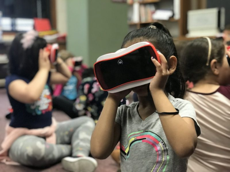 First grade students at Bryant Elementary use virtual reality goggles to view the new Bryant Elementary building opening in August.
