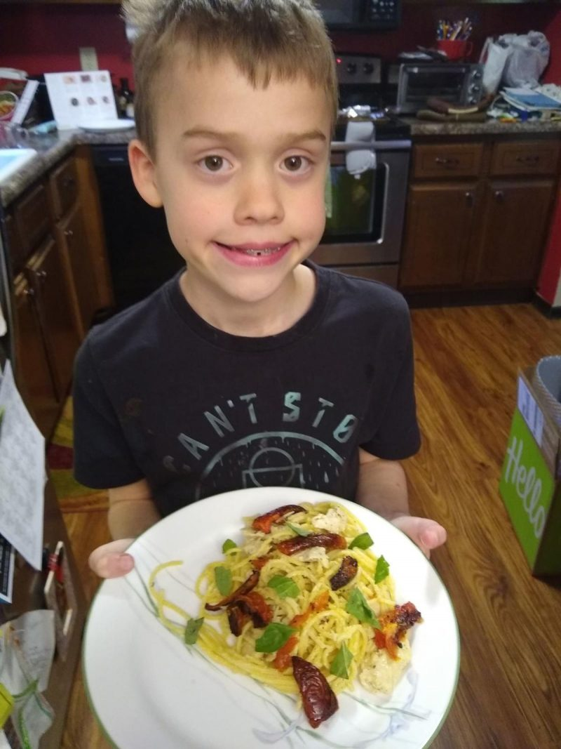 Perry Creek Elementary third-grader, Alex Hexom, shows off the creamy parmesan chicken he made for his family