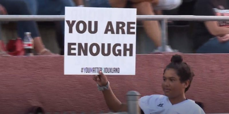 Student holding you are enough sign to raise awareness for suicide prevention.