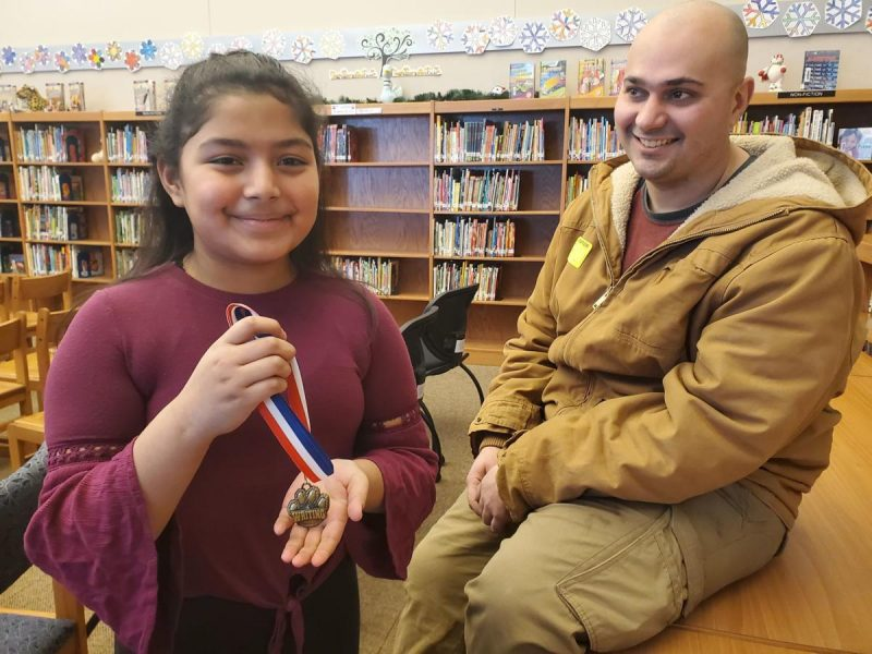 Spalding Park Environmental Sciences Elementary fourth-grader shows off medal for an Exceptional Writer award. Photo by Earl Horlyk, Sioux City Journal.