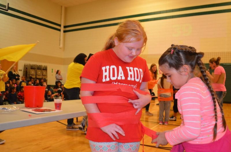 Student gets mummified by her Liberty Elementary School classmate at the Liberty Elementary House Games Photo by Earl Horlyk, Sioux City Journal