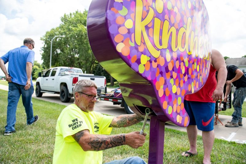 Butch Renders tightens the Kindness sign into position in front of North High School, Photo by Jesse Brothers, Sioux City Journal